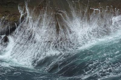 waves surging against a rocky cliff