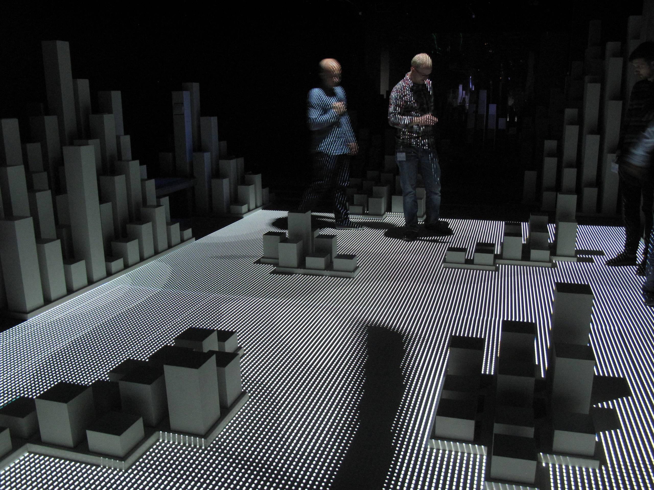 immersive installation of white sculptural columns in a dark room