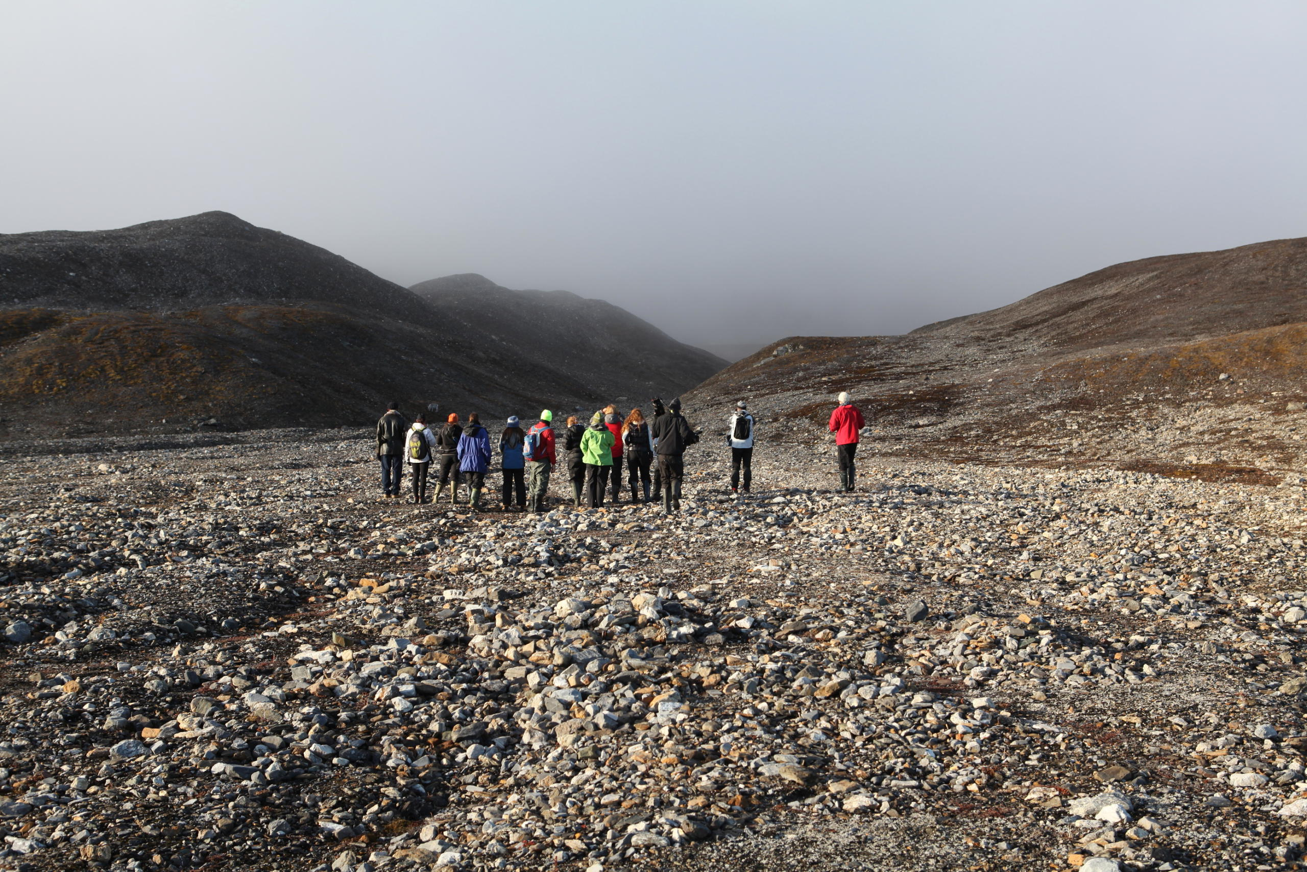 group of people in a vast tundra landscape