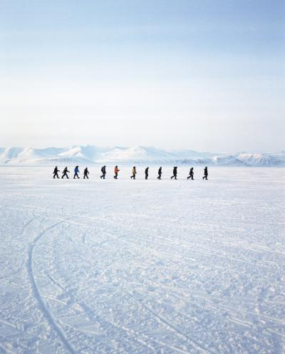 figures walk on ice in a vast Arctic landscape