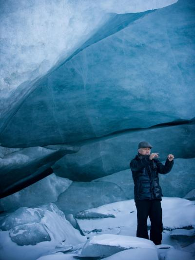 man stands in front of a glacier face