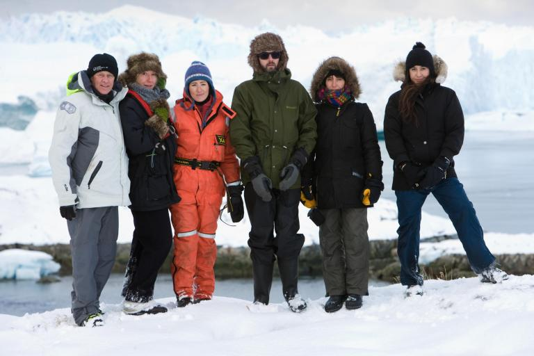 group in Arctic clothing gather in front of a glacier