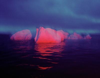 iceberg spotlit by red light