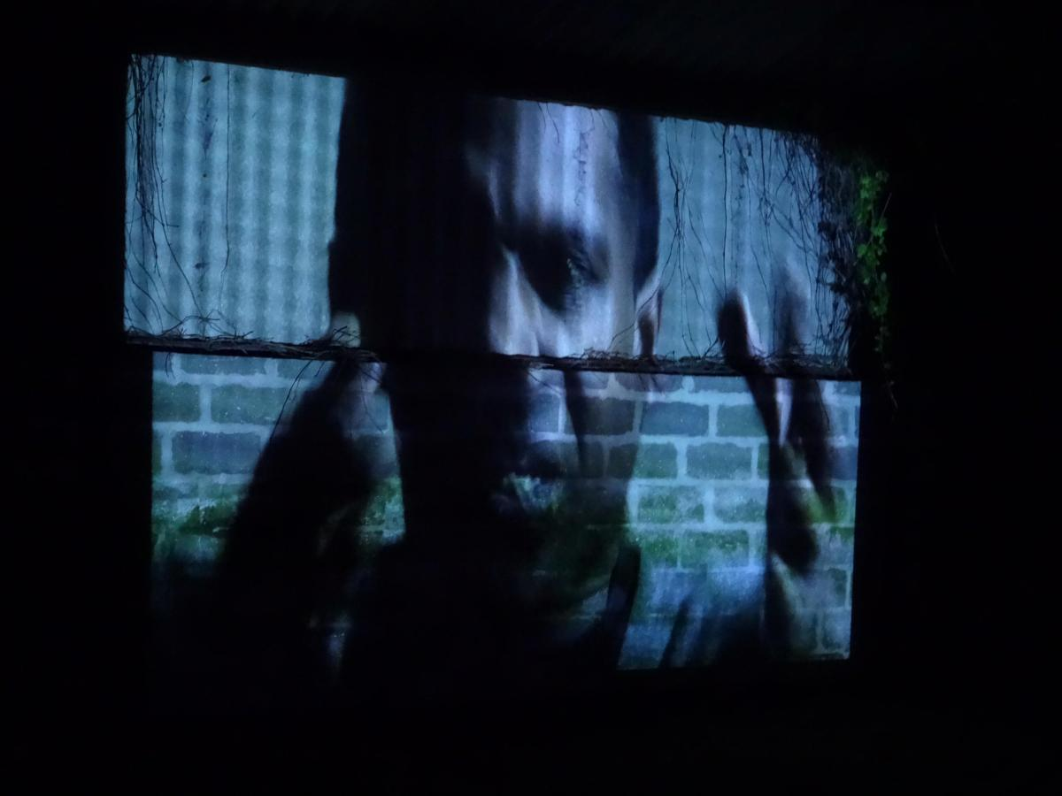 fragmented projection of a man on an urban wall