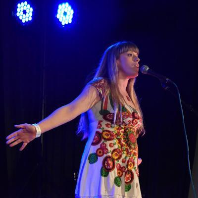 spotlit woman performing poetry