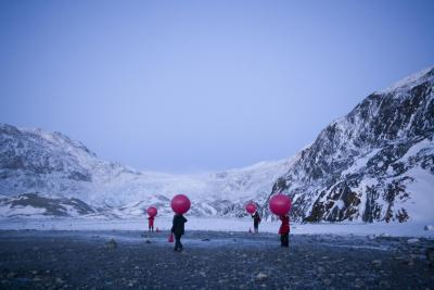 figures holding red weather balloons in Arctic landscape