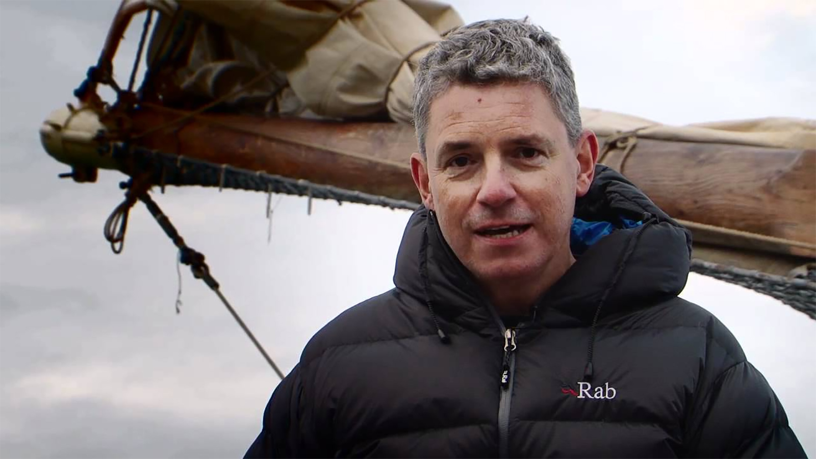 man in thermal jacket on a sailing boat