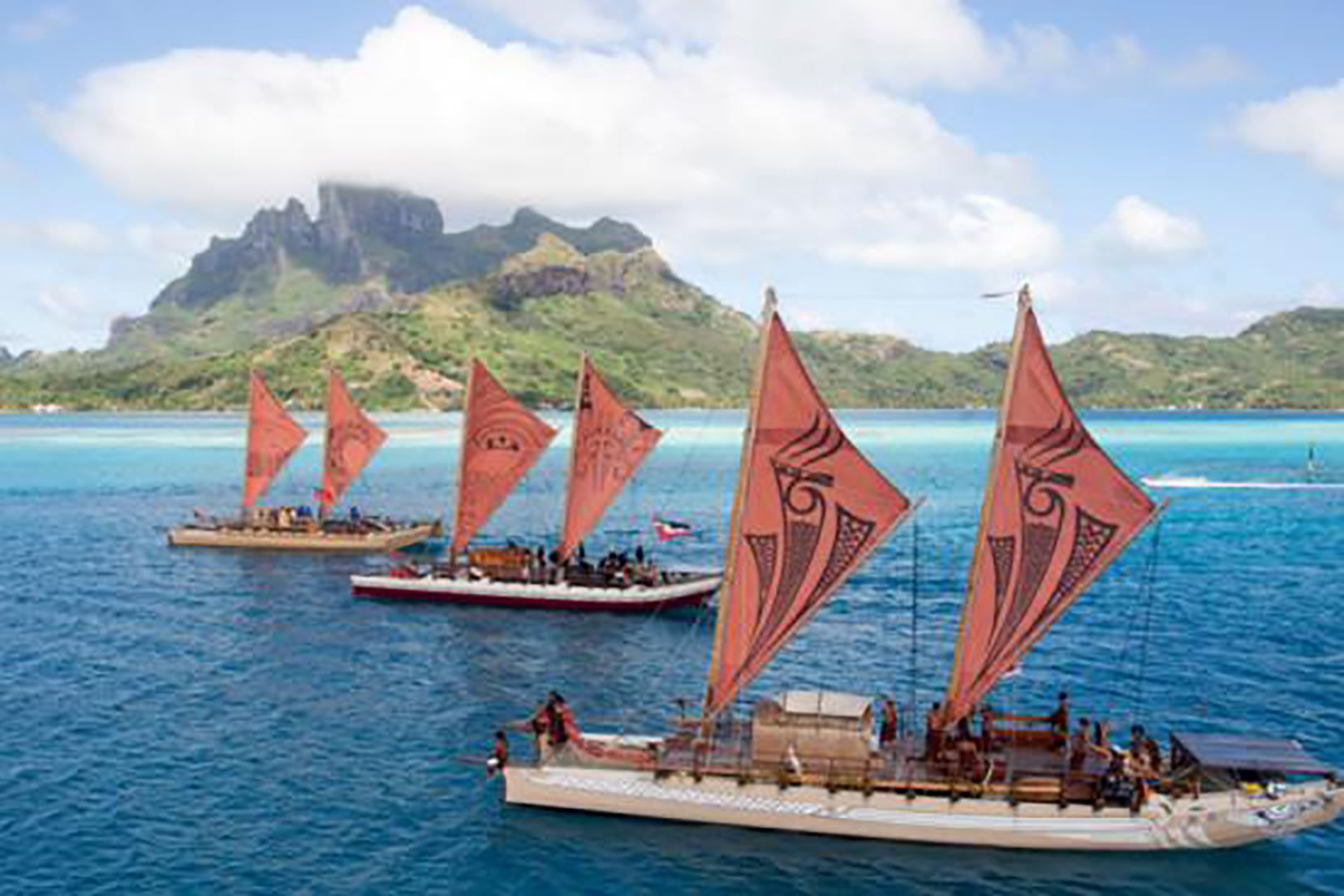 traditional sailing boats against an island backdrop