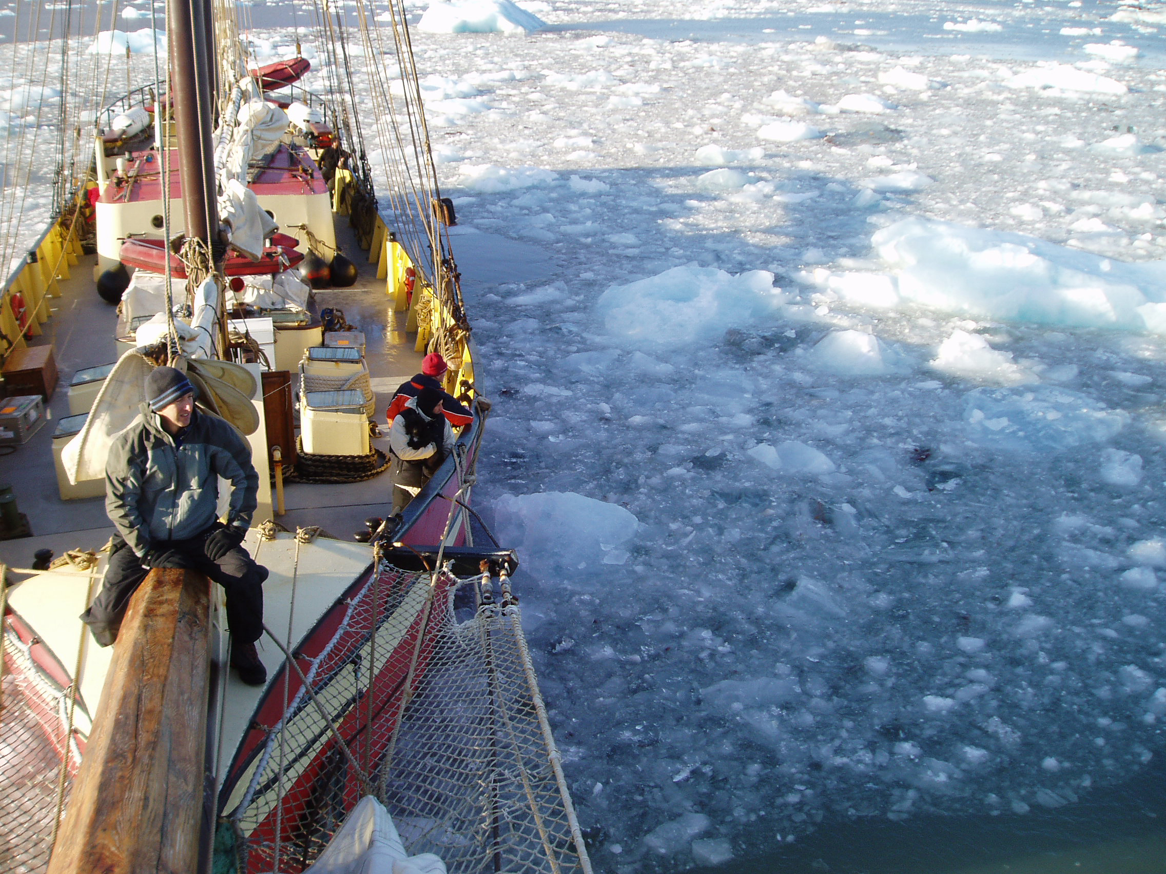 boat sails through pack ice