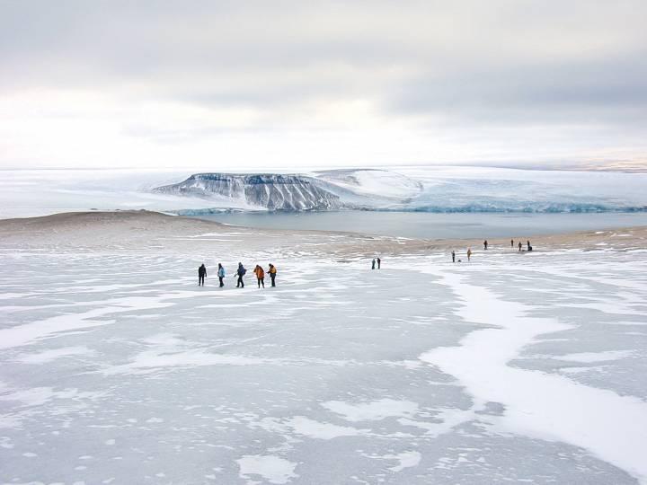 tiny figures walk on an ice sheet