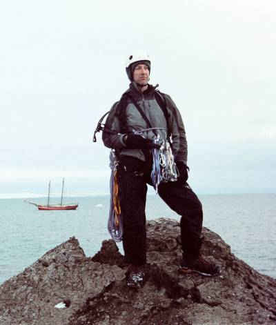 man in climbing gear on top of small mound