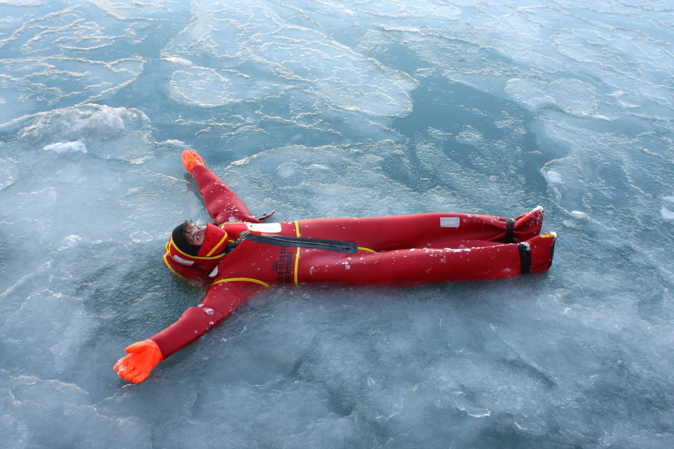 man in a survival suit floats in Arctic water