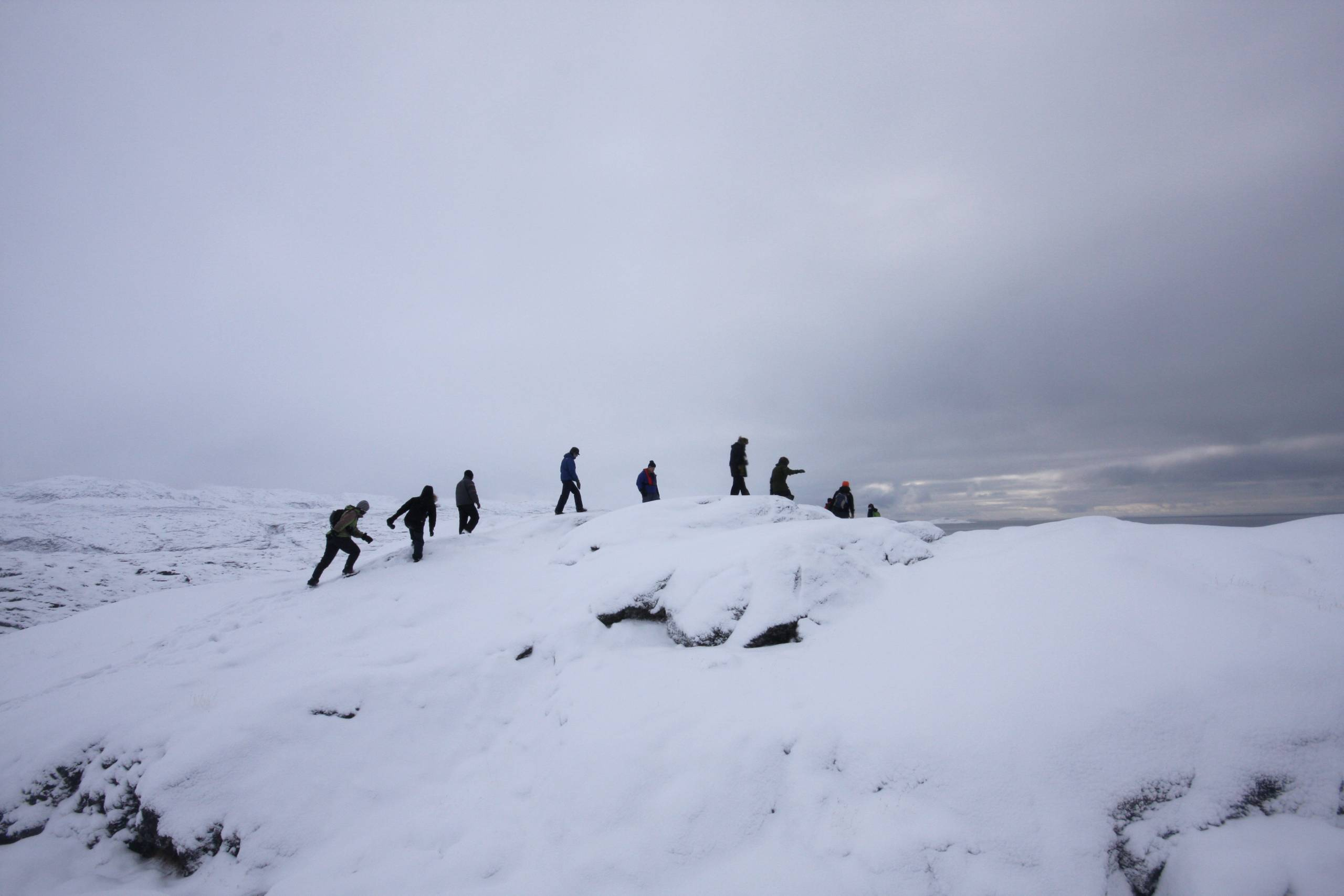 group of people climb an arctic hill