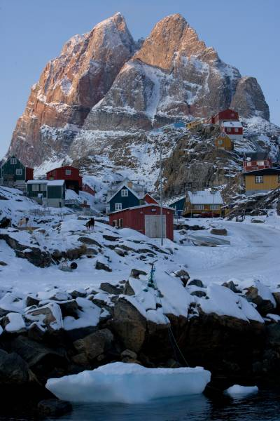 buildings dwarfed by mountains in an arctic landscape