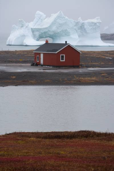 view of an iceberg dwarfing a building in the Arctic