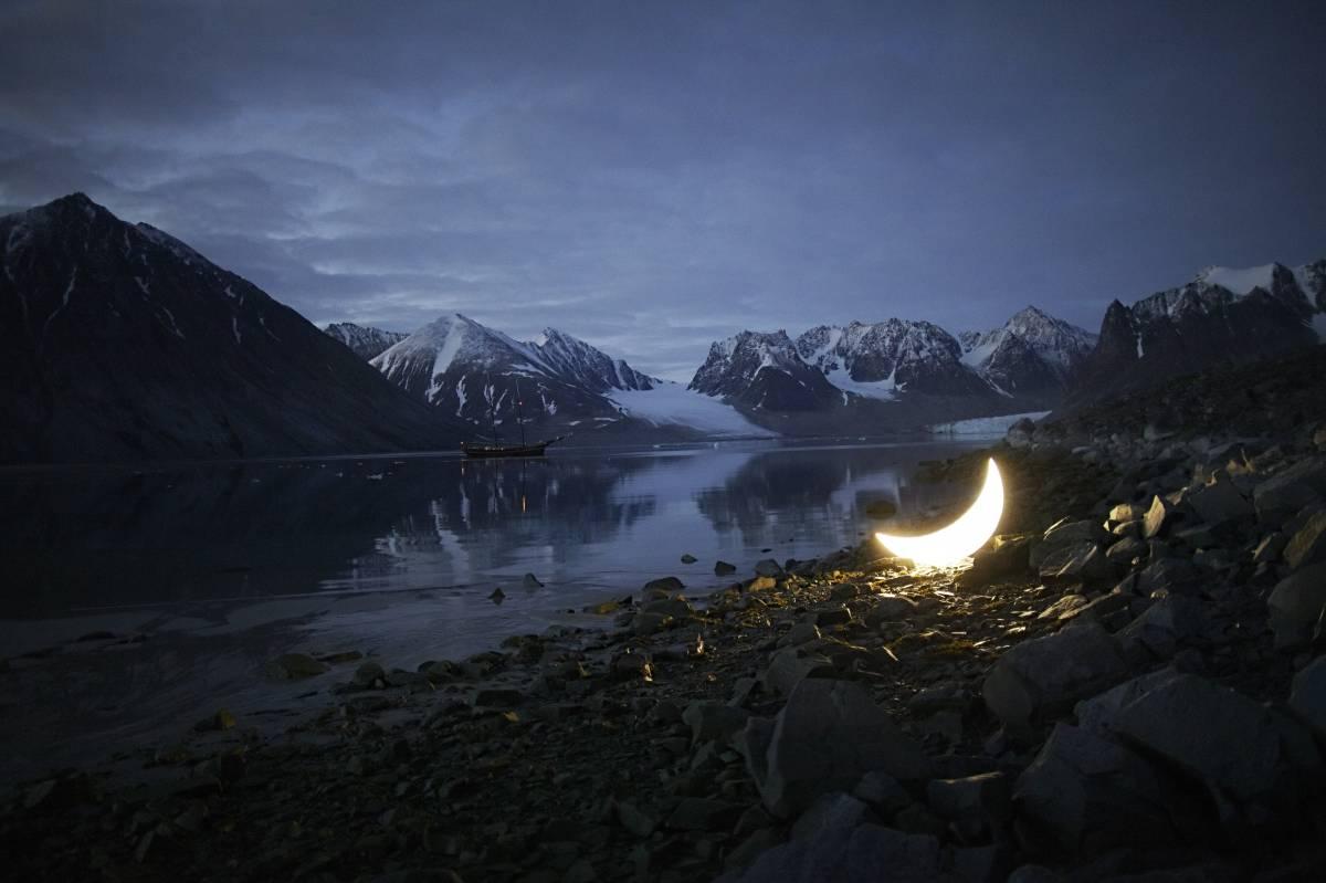 glowing moon sculpture in Arctic landscape