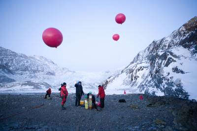 figures holding weather balloons in an Arctic landscape