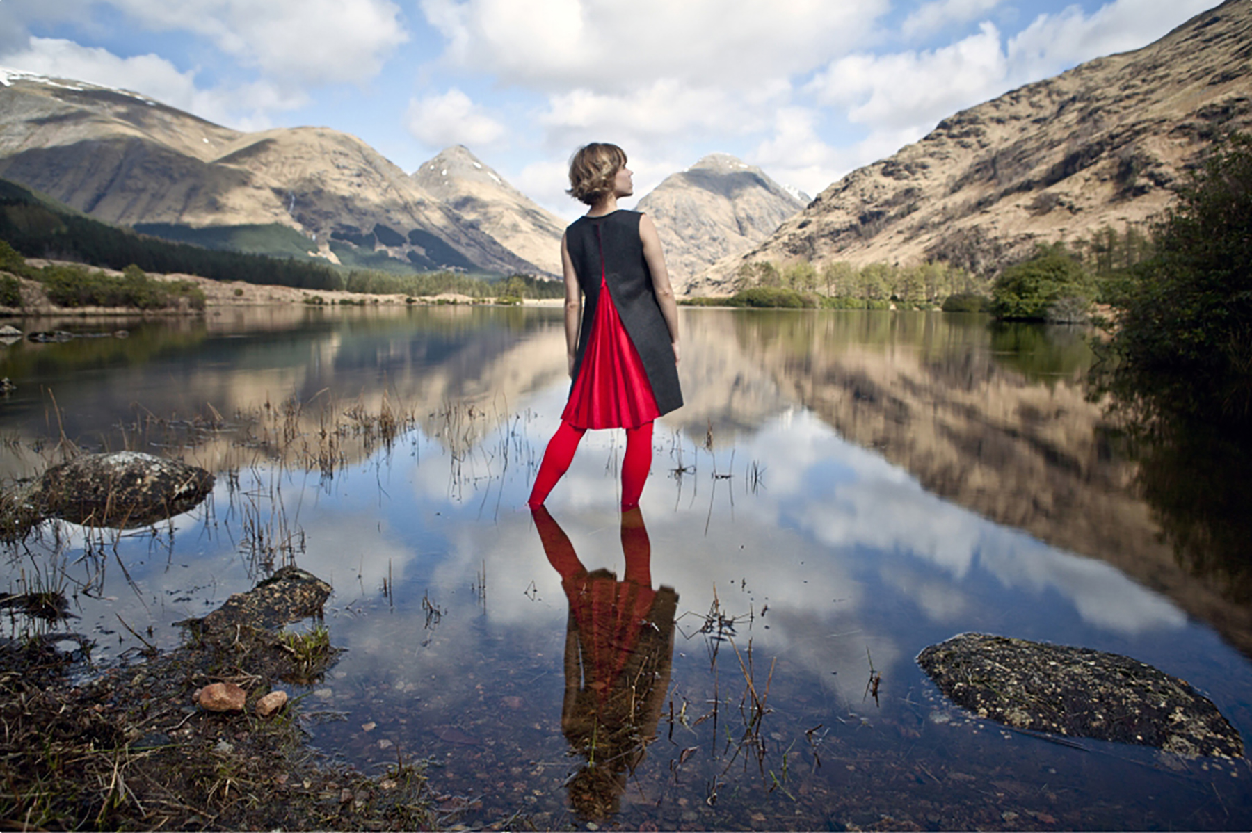 woman stands reflected in a vast lake landscape