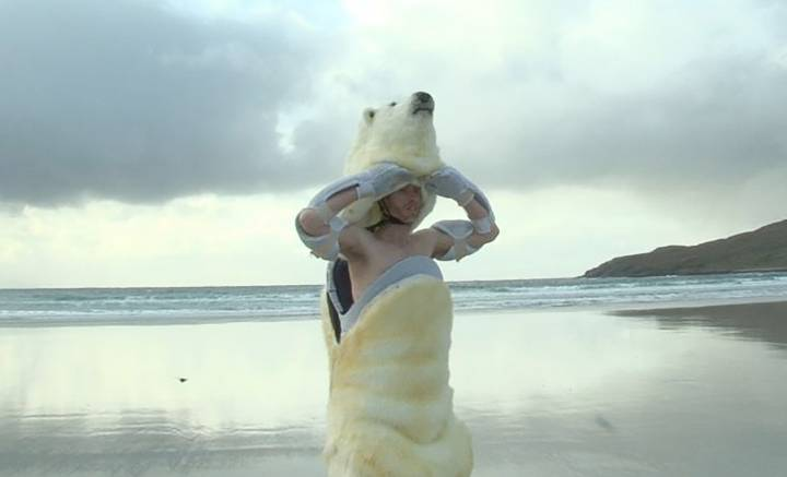 man in polar bear costume emerges from the sea