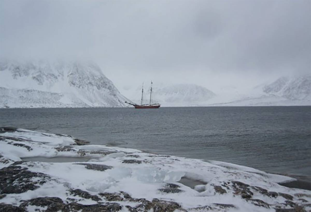 sailing boat in arctic landscape