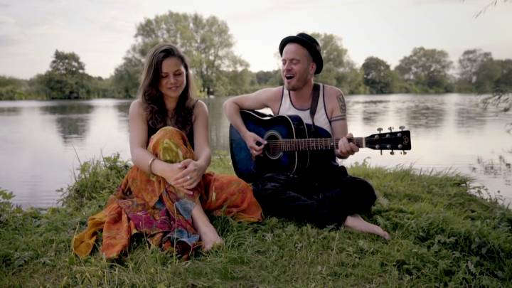 two people singing by a river bank
