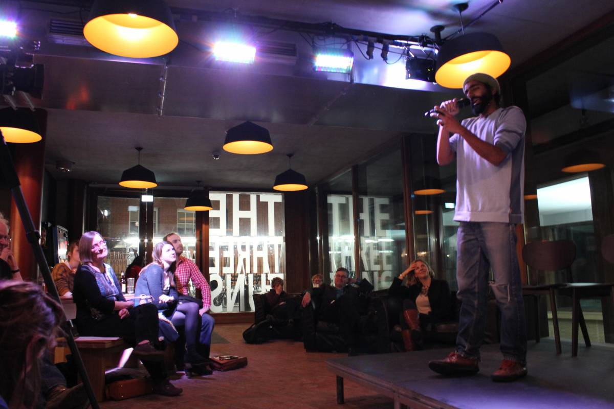 man performing poetry on intimate stage
